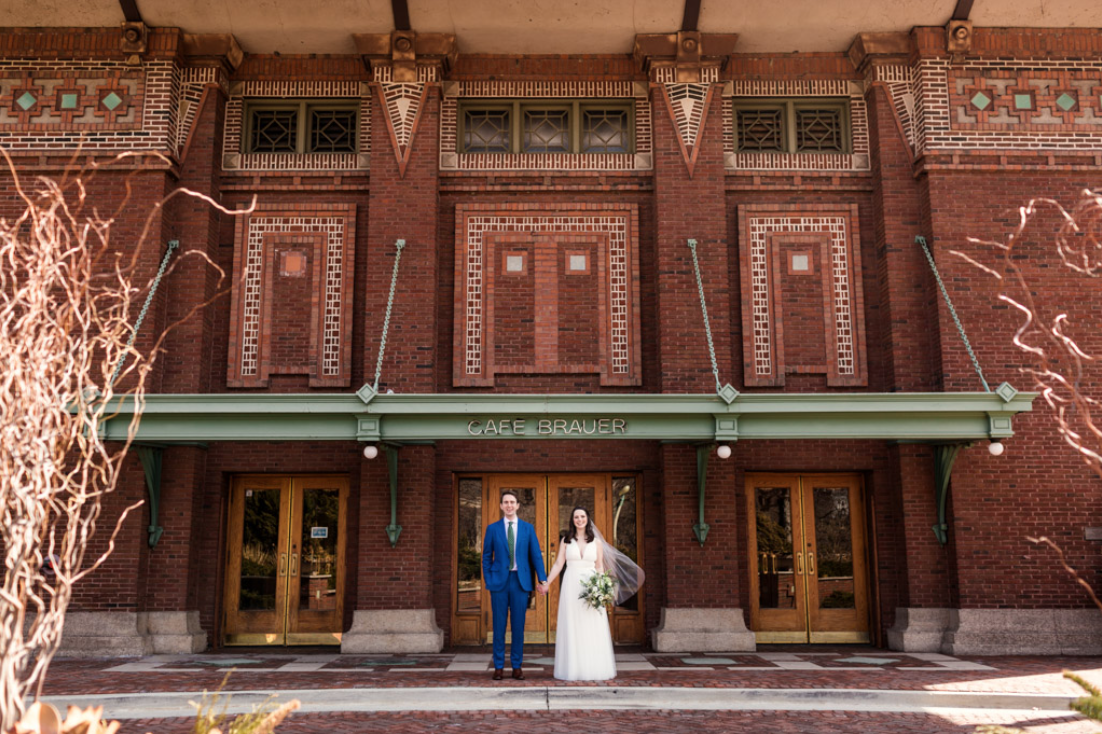 A wedding couple is holding hands and standing in front of Café Brauer in Illinois.