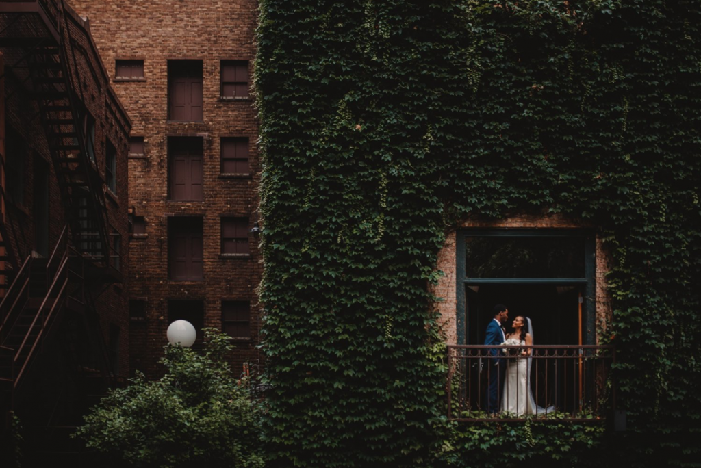 A wedding couple is standing at a balcony at the Ivy Room in Chicago, one of the wedding venues in Illinois.