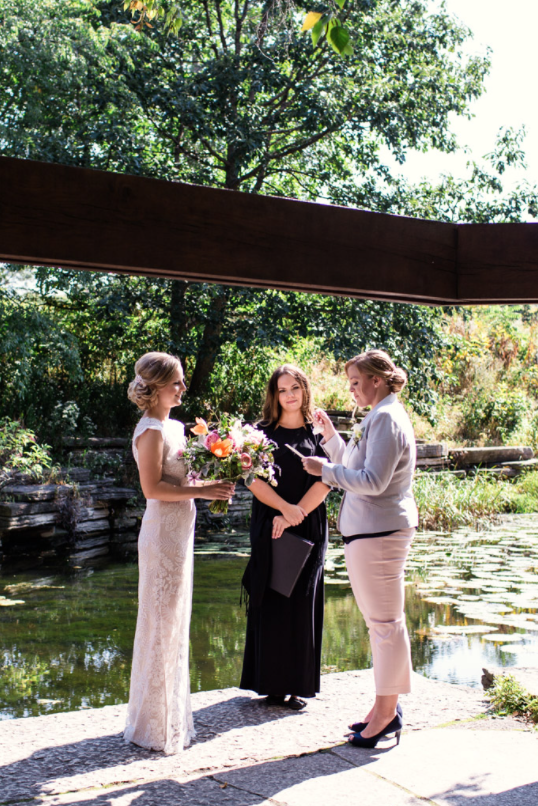 A wedding couple is getting married at the Alfred Caldwell Lily Pool in Chicago, Illinois.