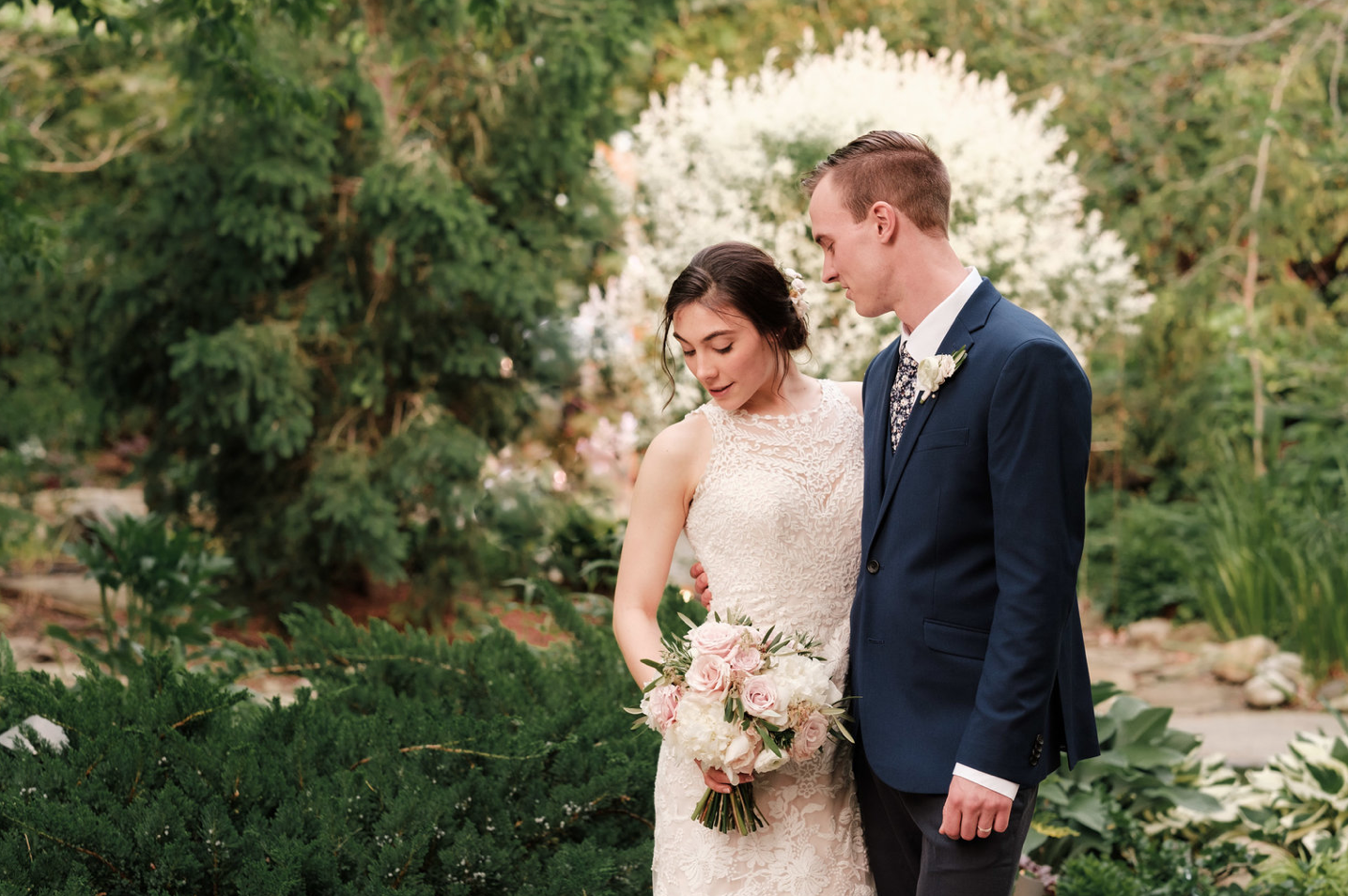 A wedding couple is standing at the Gardens of Woodstock in Illinois.
