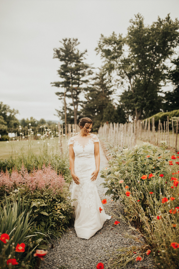 A bride is walking next to flowers at the Meadowburn Farm in New Jersey.