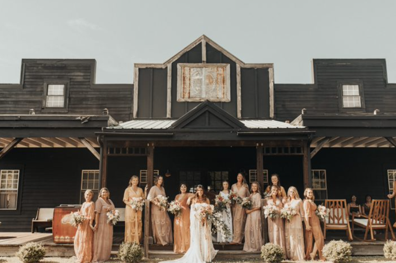 A bride and her bridesmaids are standing in front of Everly at Railroad in New Jersey.