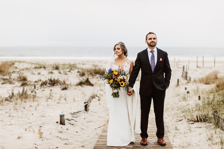A wedding couple is standing at the beach and holding hands, next to the Daymark wedding venue.