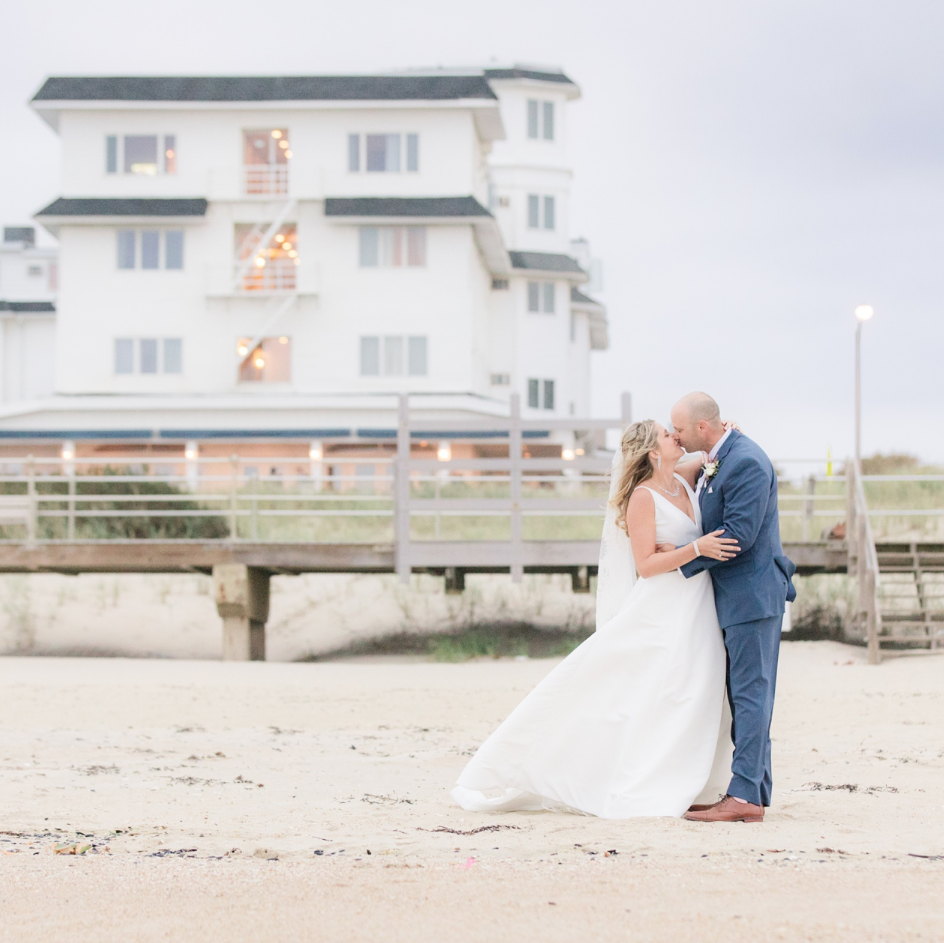 A wedding couple is kissing each other and standing on the beach at the Breakers on the Ocean Hotel in New Jersey.