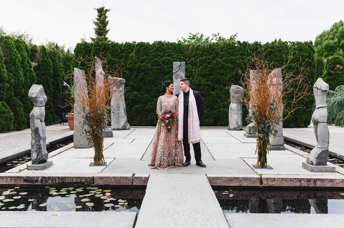 A wedding couple is standing at the Grounds of Sculpture, one of the New Jersey wedding venues.