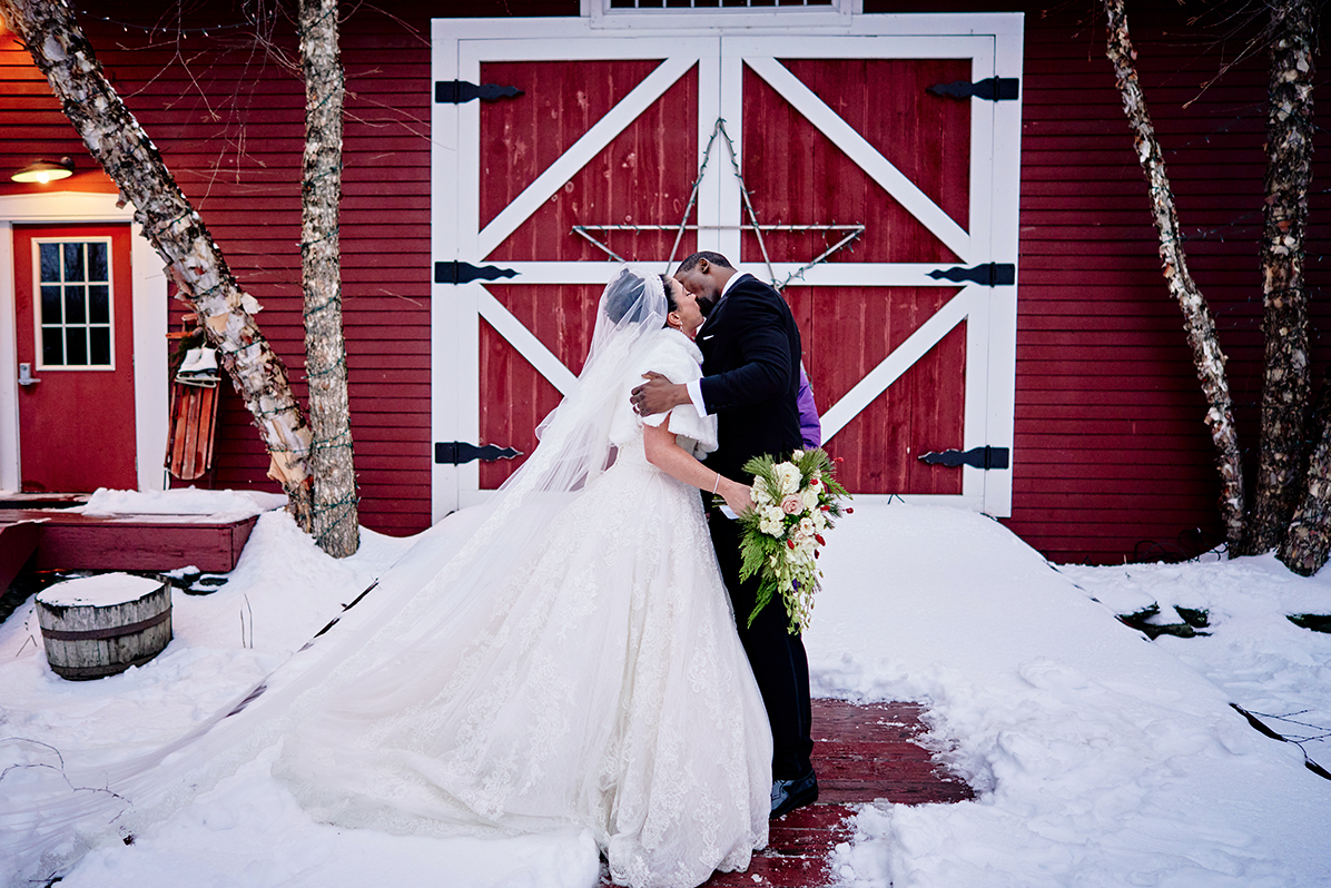 A wedding couple is kissing each other in front of a red barn at the 1824 House in Vermont.