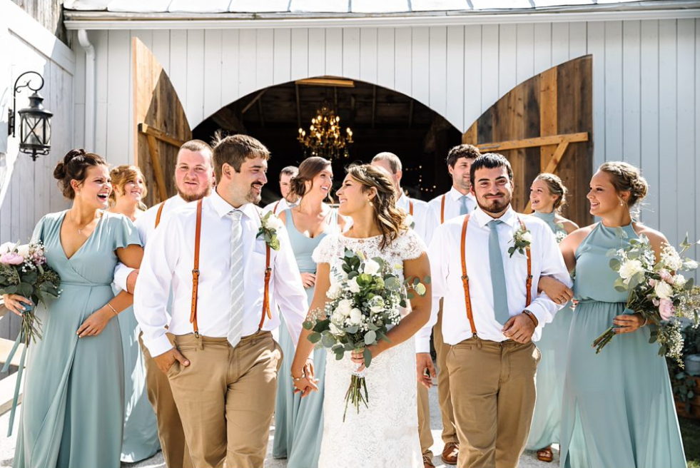 A wedding couple and their guests are walking out of the Vermint Swiss and Bloom Farm.
