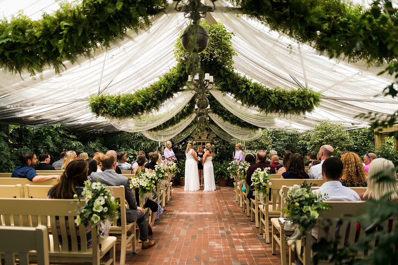 A wedding couple is standing at the end of the aisle at the Conservatory in Saint Charles, one of the wedding venues in Missouri.
