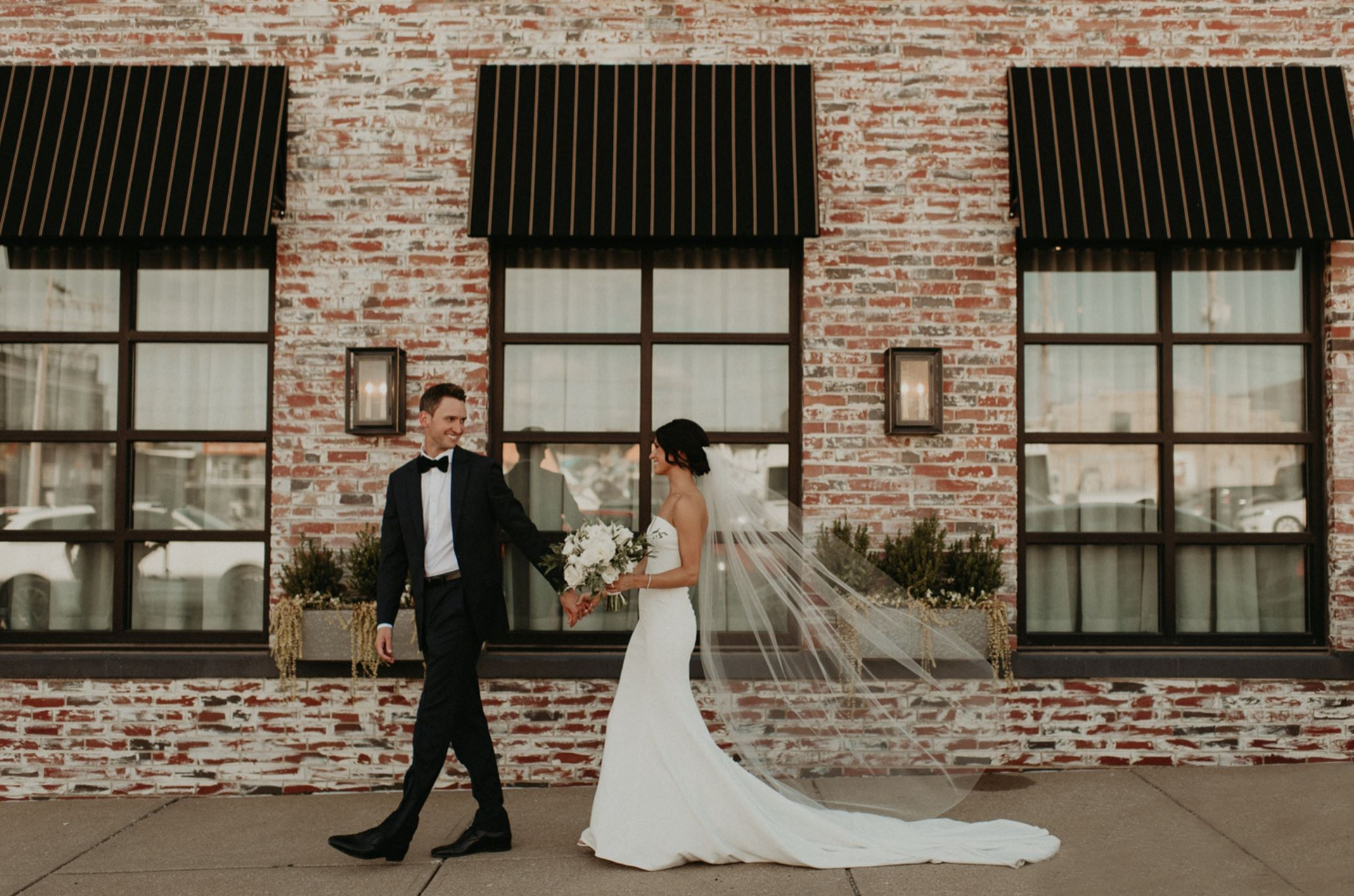 A wedding couple is holding hands and walking along the Cherry Hall in Kansas City, Missouri.