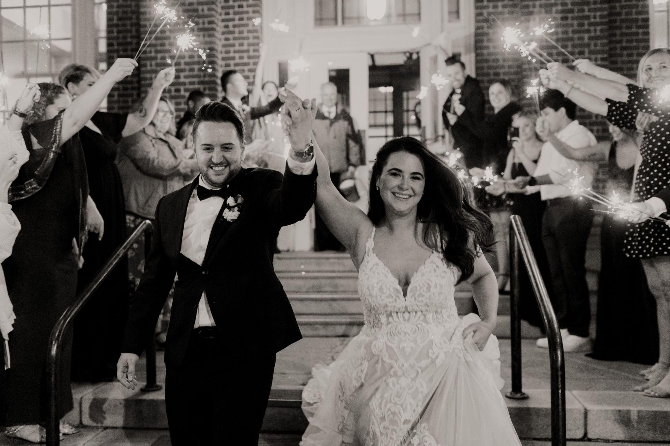 A wedding couple is walking down the stairs with their guests cheering at them, at the Festivities Event Center in Oklahoma.