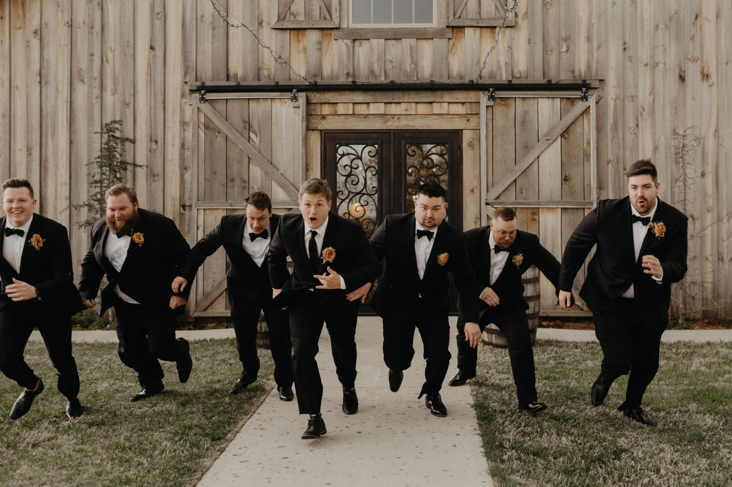 A groom and his groomsmen are running in front of the Rustic Rose Barn in Oklahoma.