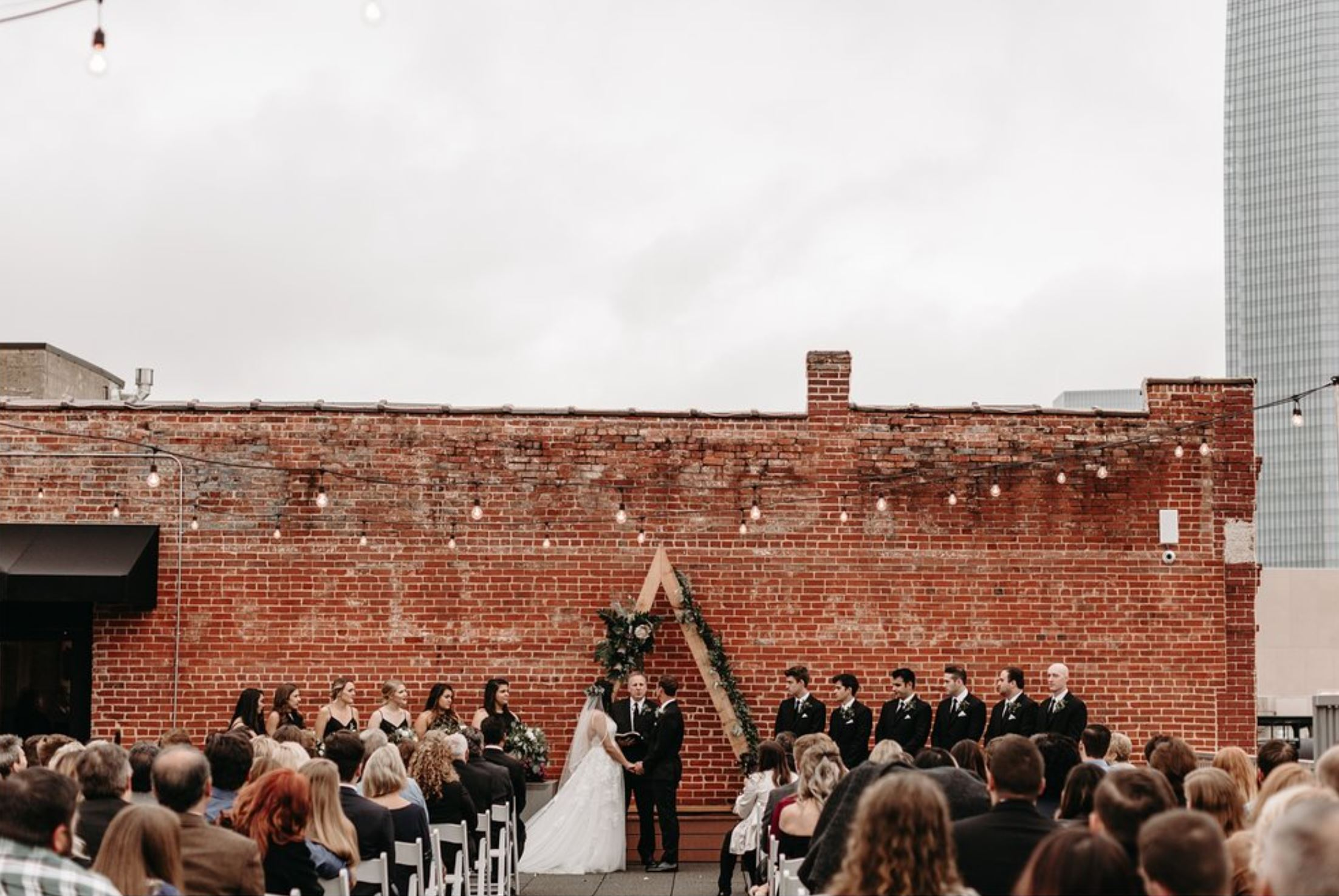 A wedding couple is getting married and is standing in front of a brick wall at Skyline on Brickwotn Canal in Oklahoma.