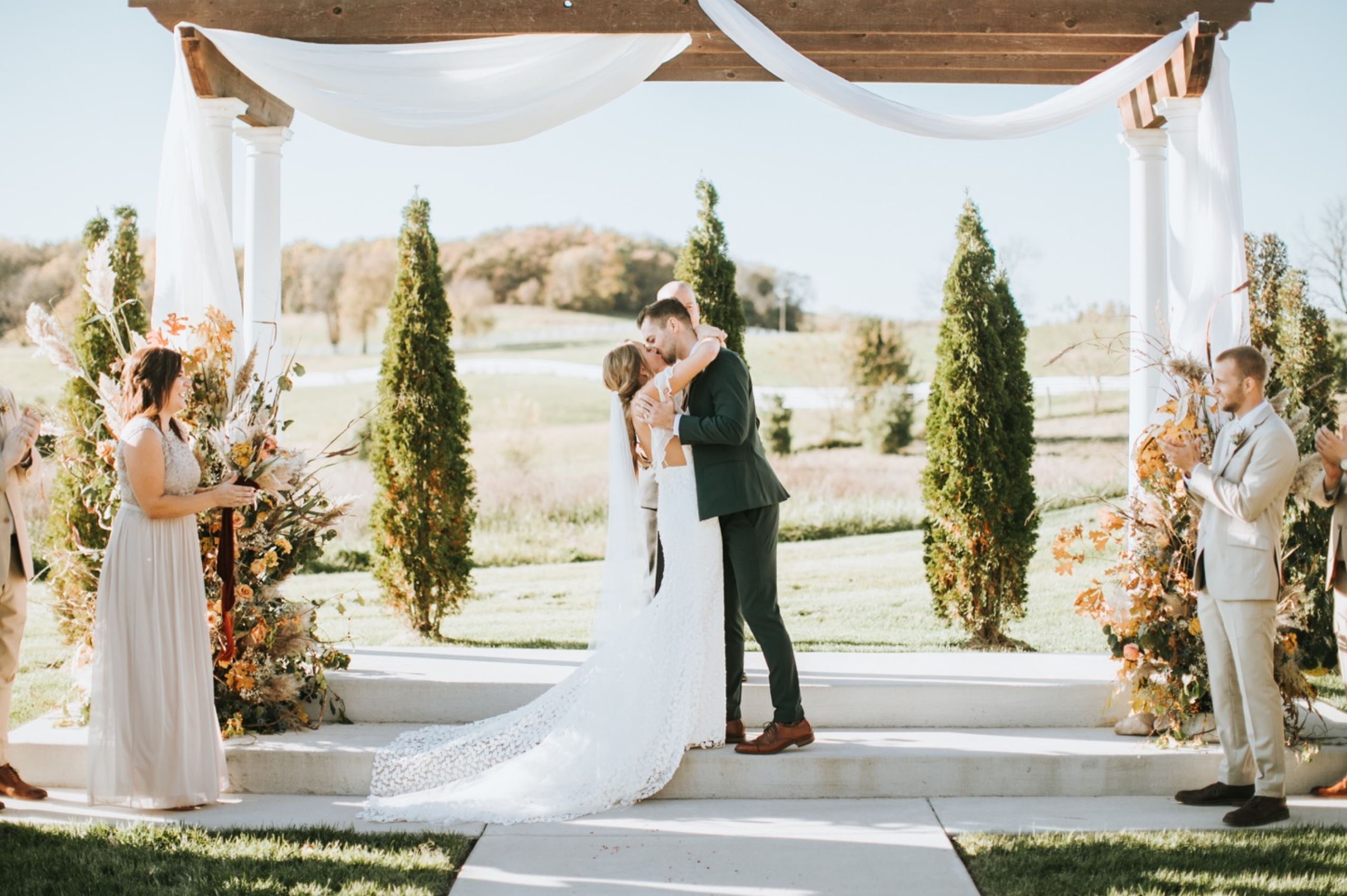 A wedding couple is kissing each other at the Fields at 1890 in Missouri.