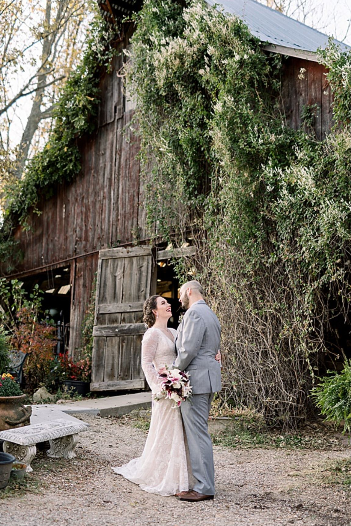 A wedding couple is standing in front of a barn at Paradise Park in Missouri.