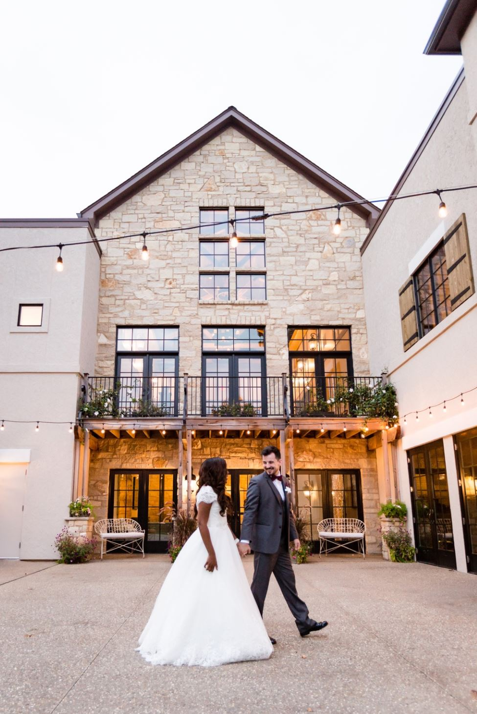 A wedding couple is holding hands at the Silver Oaks Chateau in Missouri.