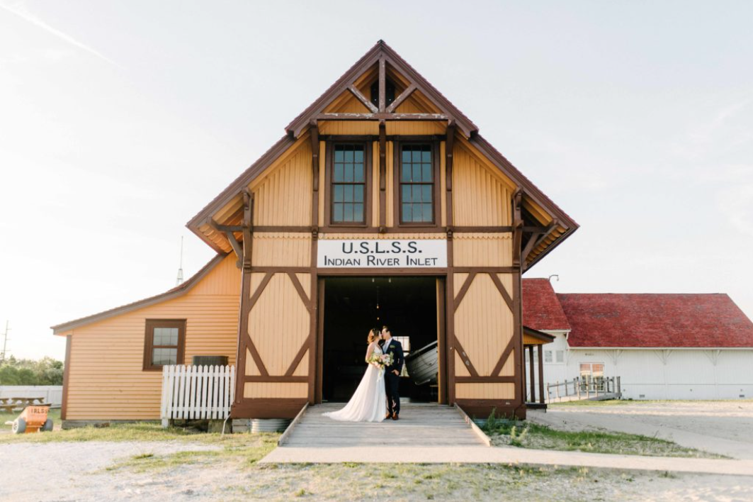 A wedding couple is kissing each other in front of the Indian River Life-Saving Station, one of the wedding venues in Delaware.