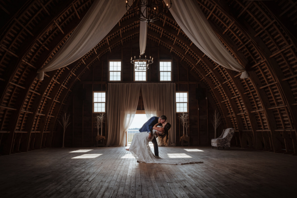 A wedding couple is kissing each other in a barn.