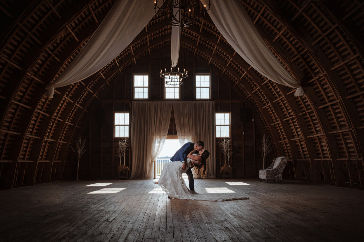 A wedding couple is kissing each other in a barn, one of the wedding venues in Delaware..