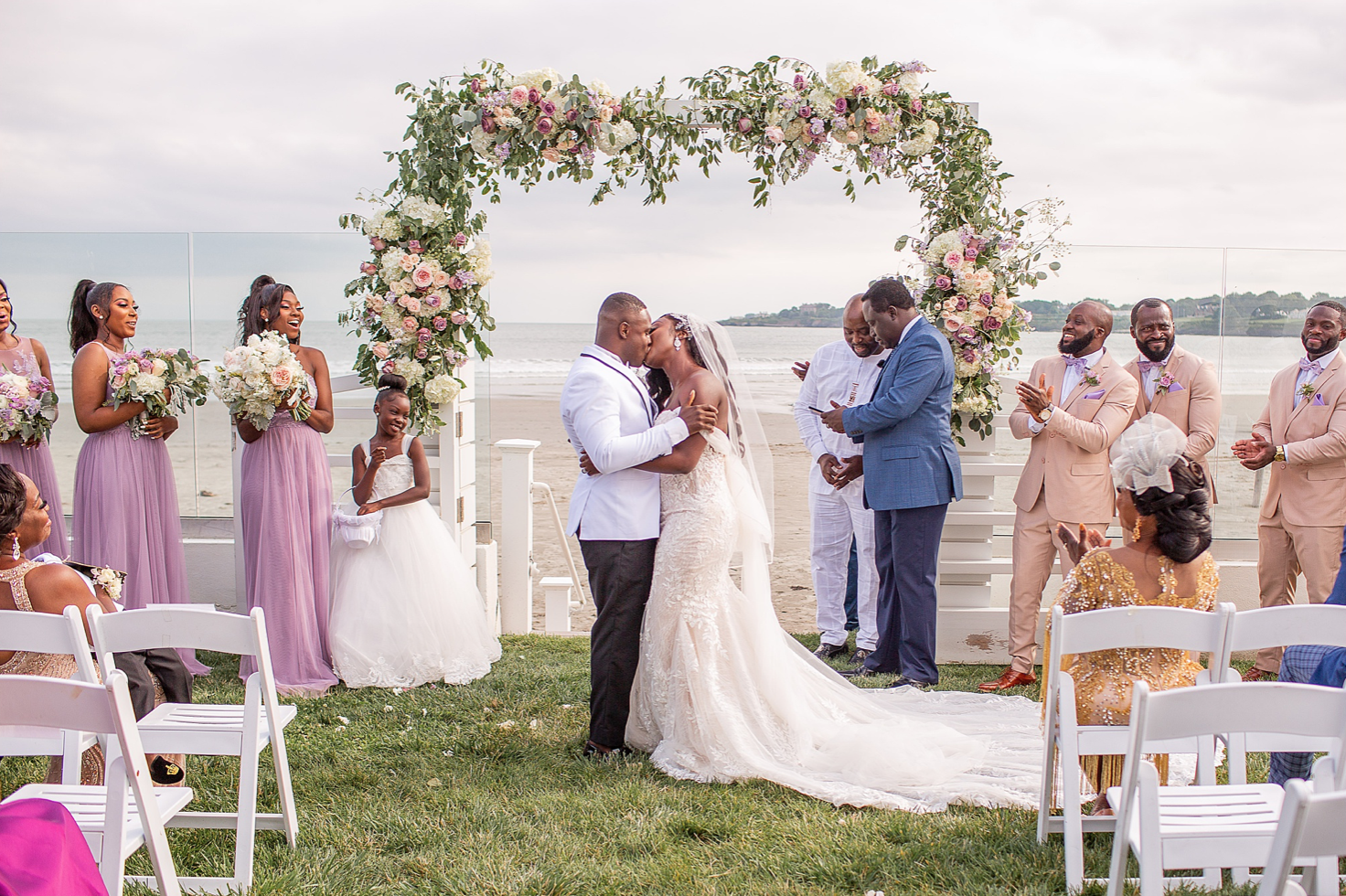 A wedding couple is kissing each other at the Newport Beach House and their guests are cheering.