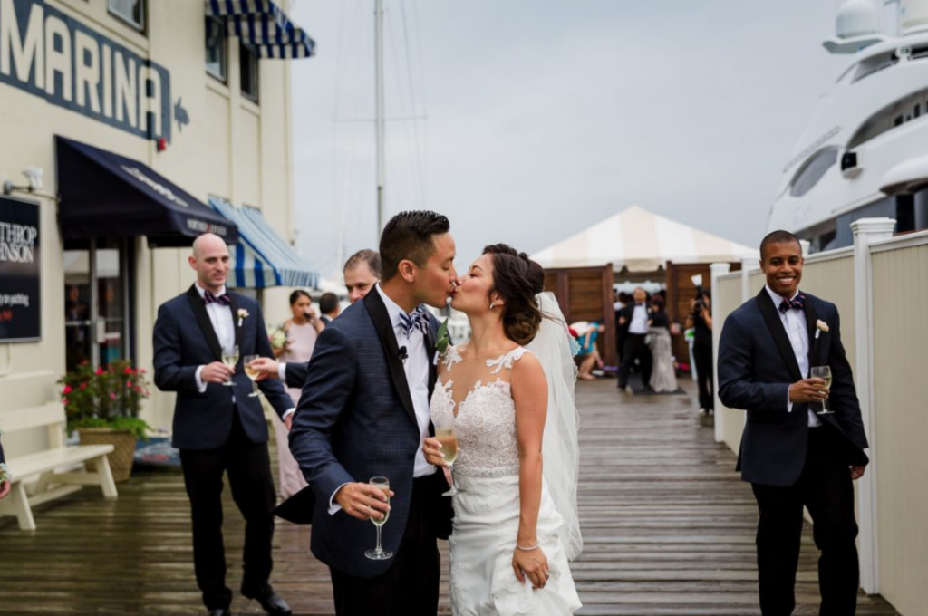 A wedding couple is kissing each other at the regatta Place in Newport, one of the wedding venues in Rhode Island.