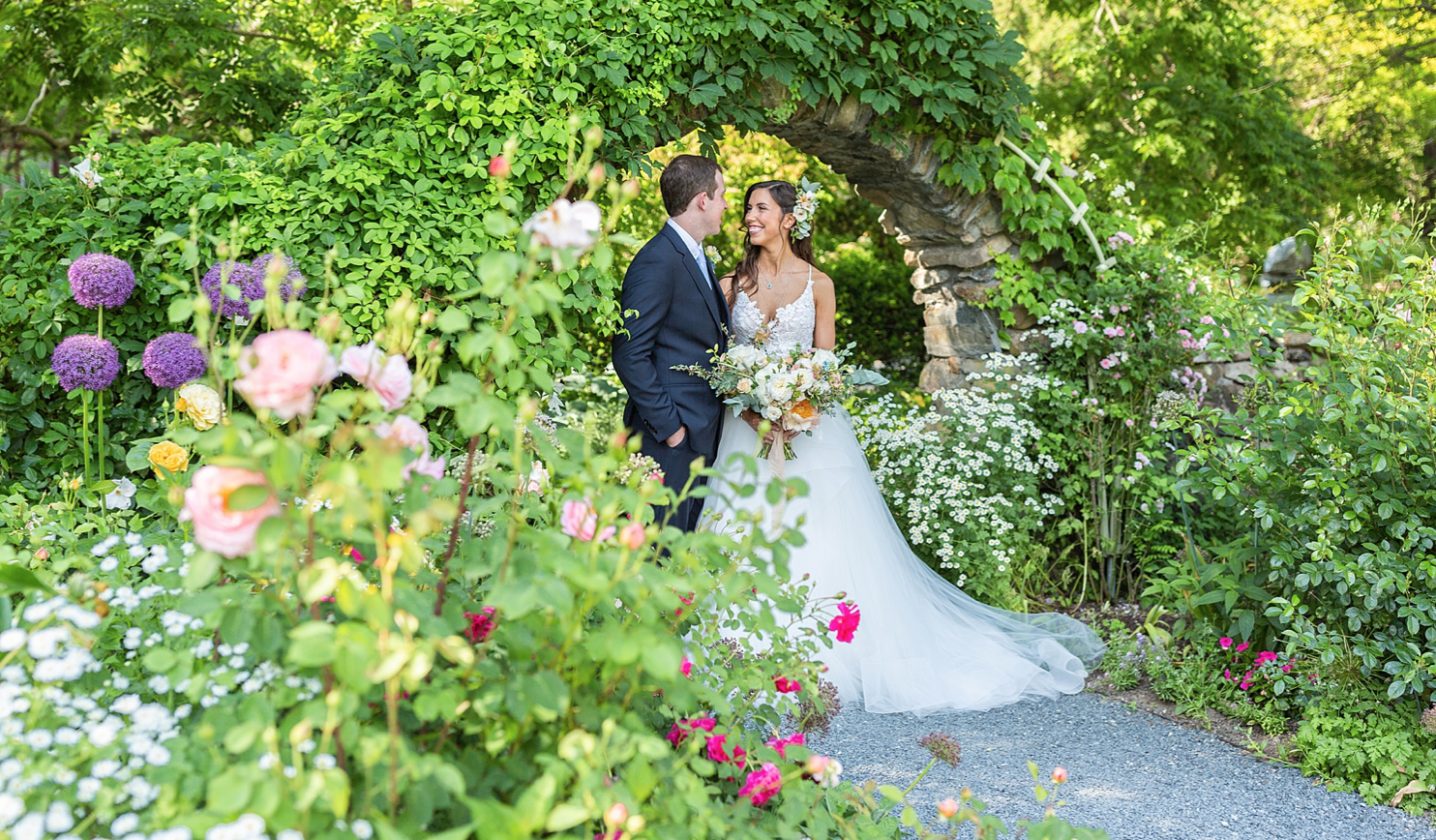 A wedding couple is standing in a beautiful garden with lots of blooming flowers.