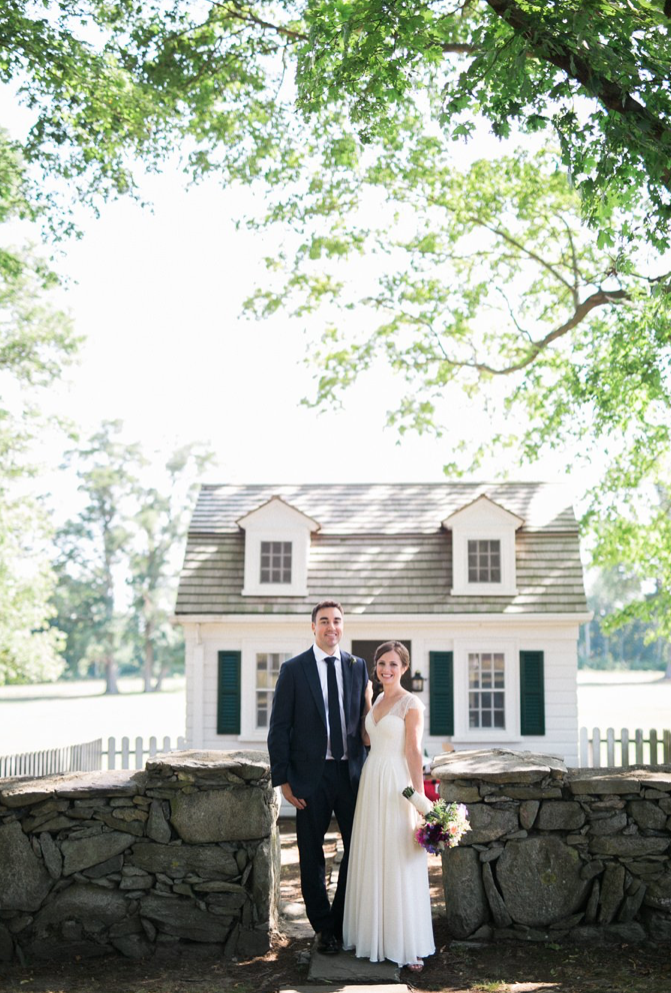 A wedding couple is standing at the Mount Hope Farm in Bristol, Rhode Island.