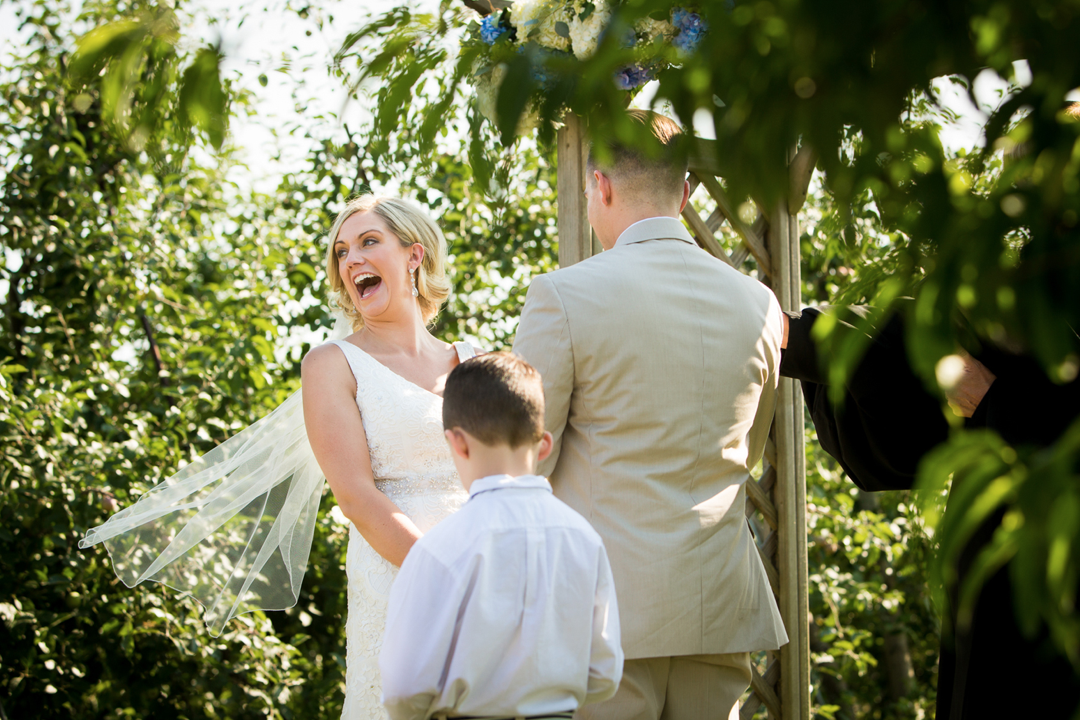 A wedding couple is getting married at the Sweet Berry Farm in Rhode Island and a child is standing next to them.