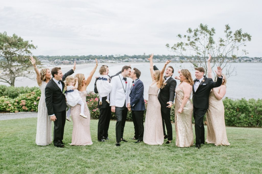 A wedding couple is kissing each other and their bridesmaids and groomsmen are cheering.