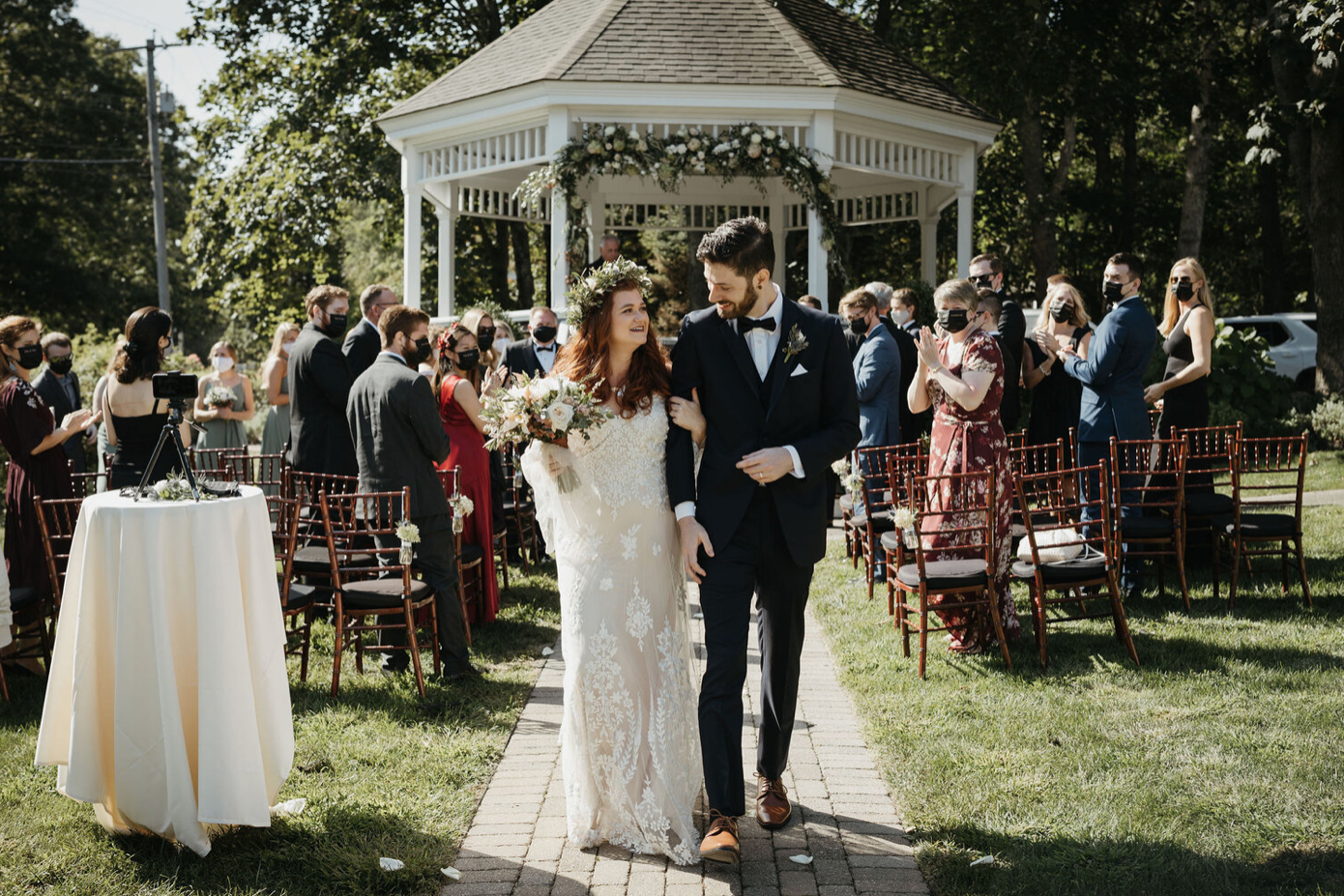 A wedding couple is standing in front of a gazebo and their guests are sitting behind them.