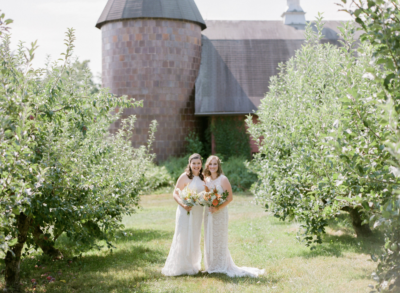 A wedding couple is standing in front of the Quonquont Farm, one of the wedding venues in Massachusetts.