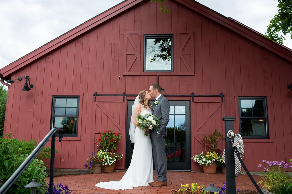 A wedding couple is kissing each other and standing in front of the Barn at Wight Farm.