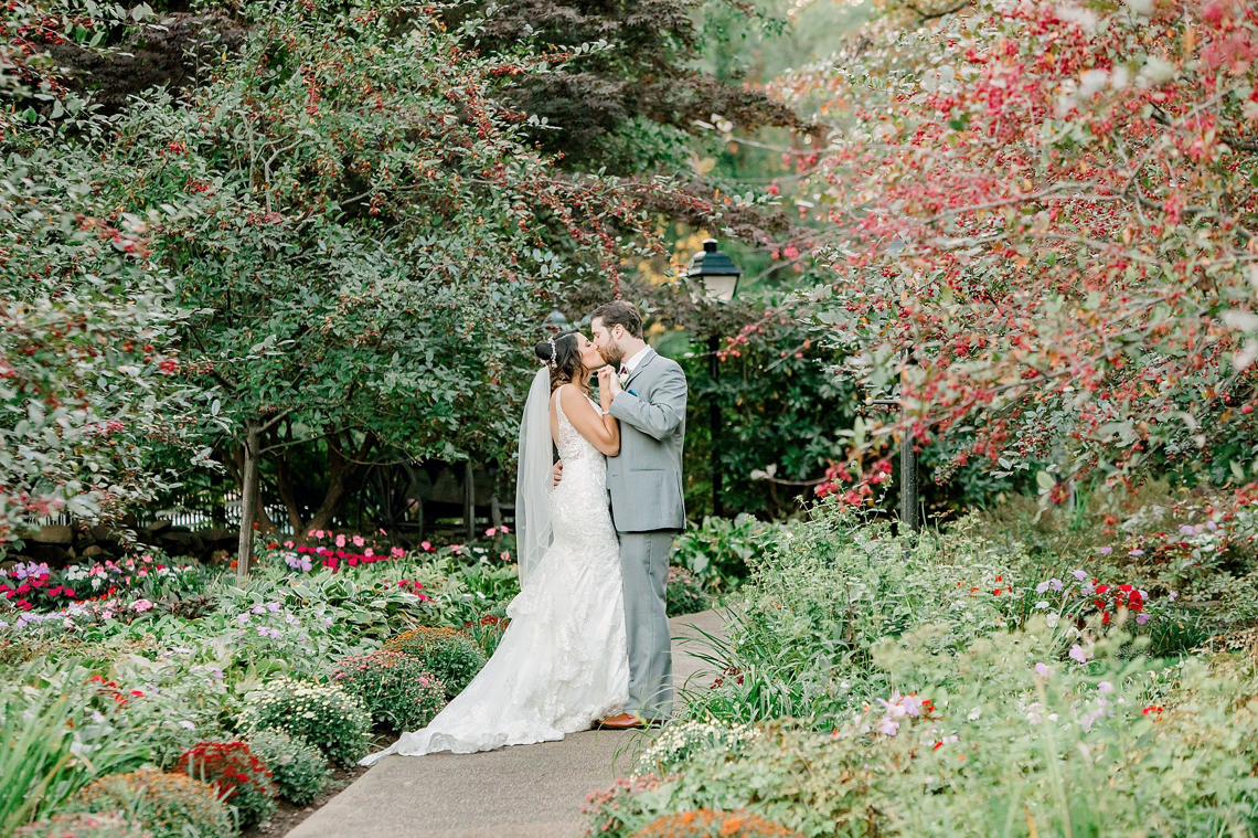 A wedding couple is kissing each other at Independence Harbor.