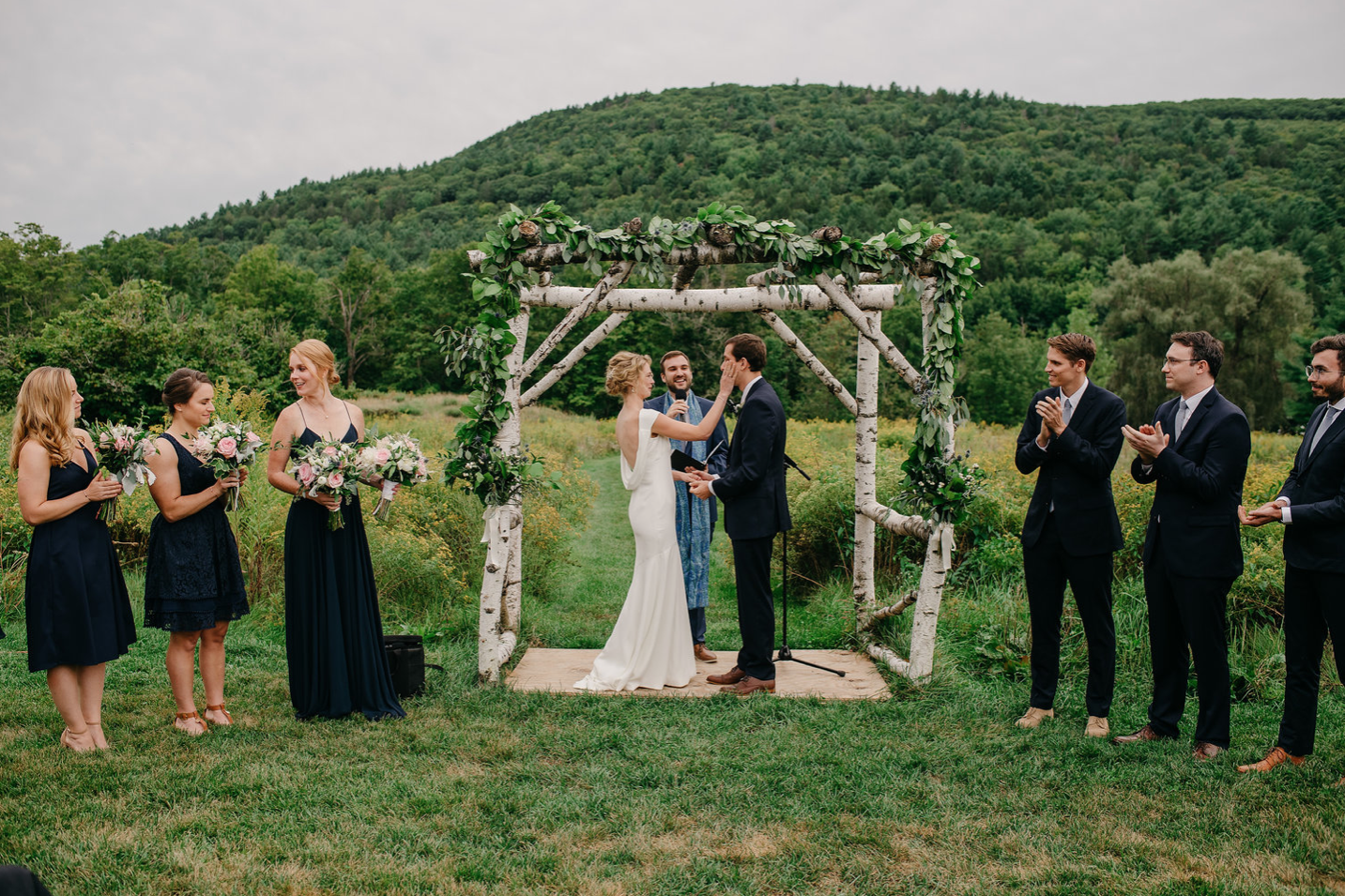 A wedding couple and their bridesmaids and groomsmen are standing at the altar.