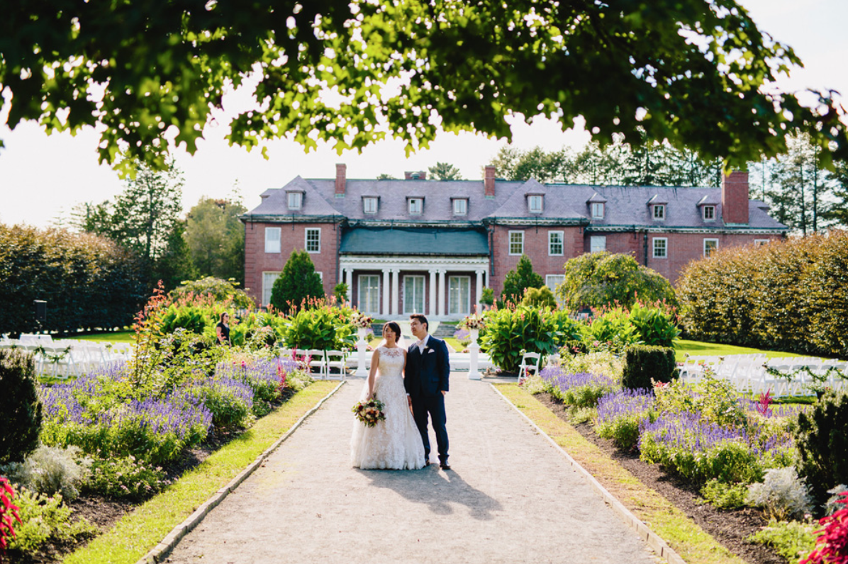 A wedding couple is holding hands and standing at the Gardens at Elm Bank.