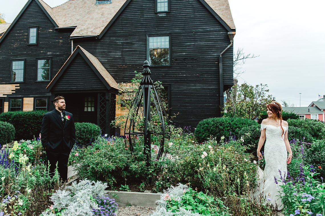 A wedding couple is standing in the front yard of a house.