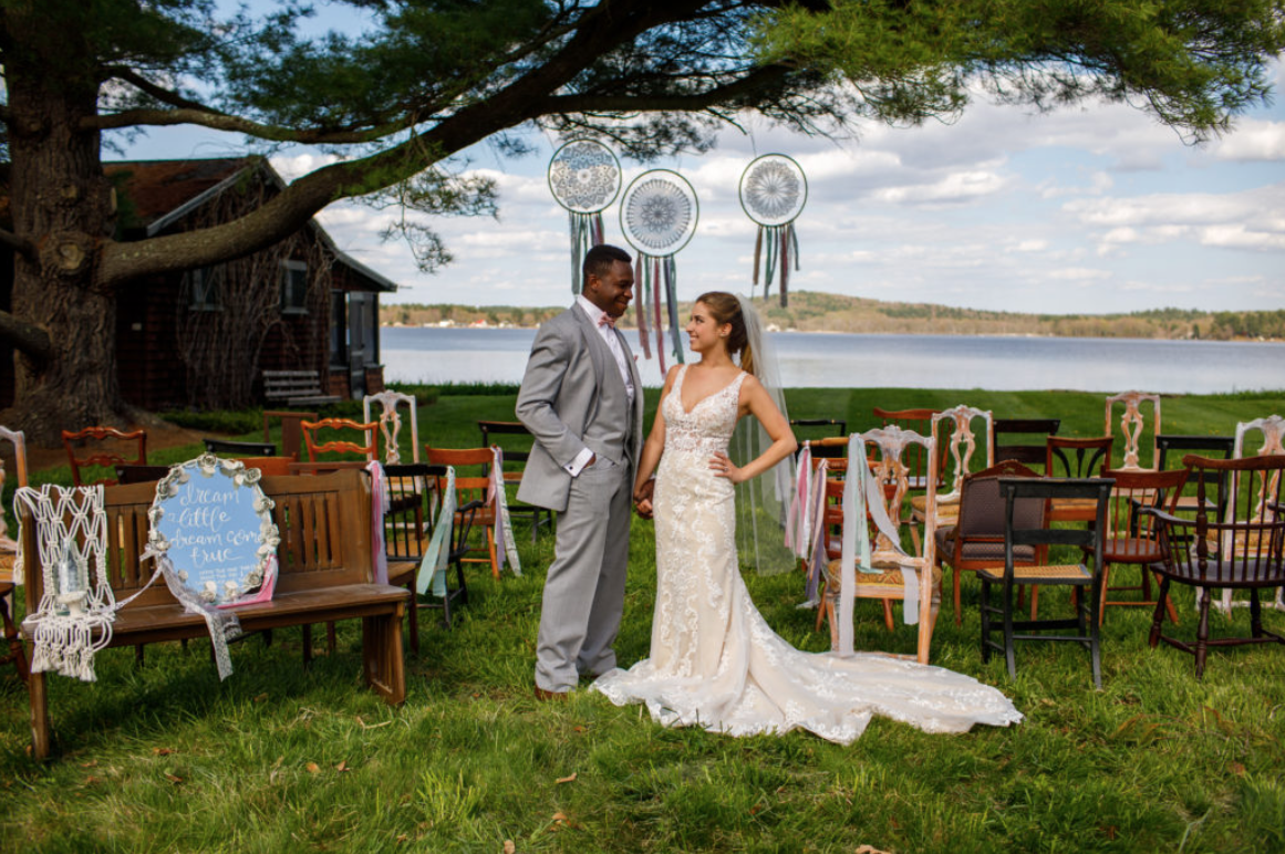 A wedding couple is standing next to a lake at the Oakholm Farm Estate.