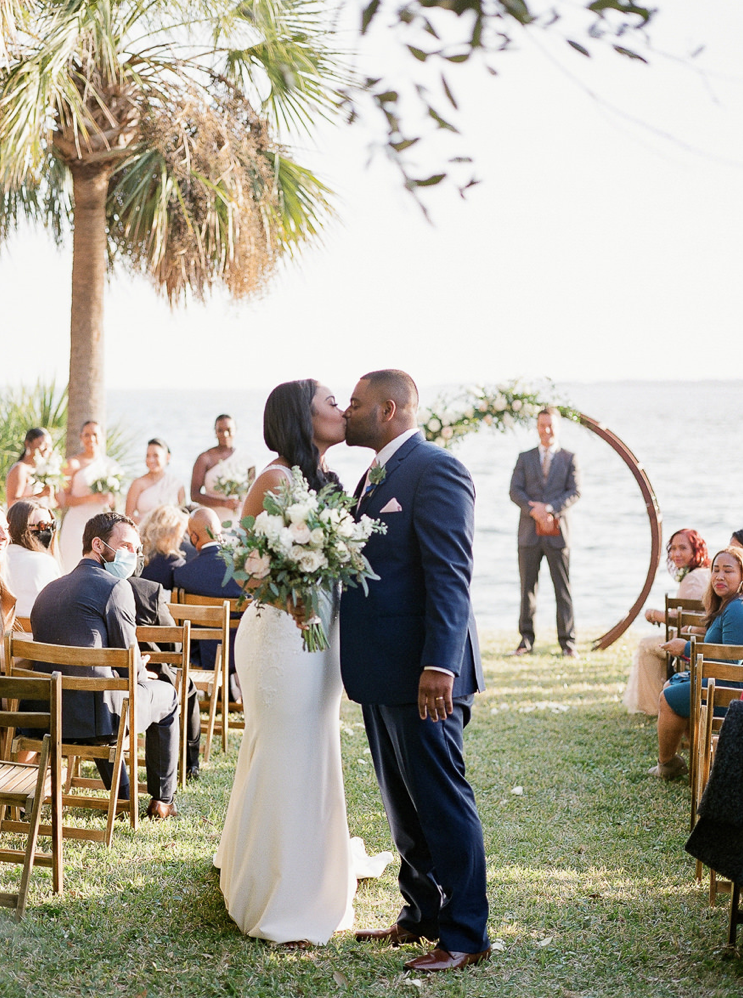 A wedding couple is kissing each other at the Cottages on Charleston Harbor.