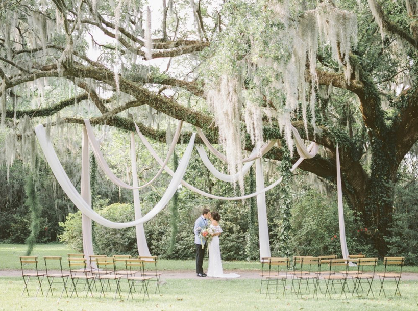 A wedding couple is kissing each other under a tree.