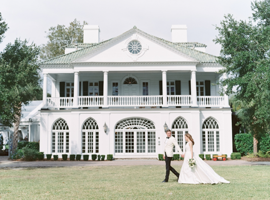 A wedding couple is walking in front of Lowndes Grove.