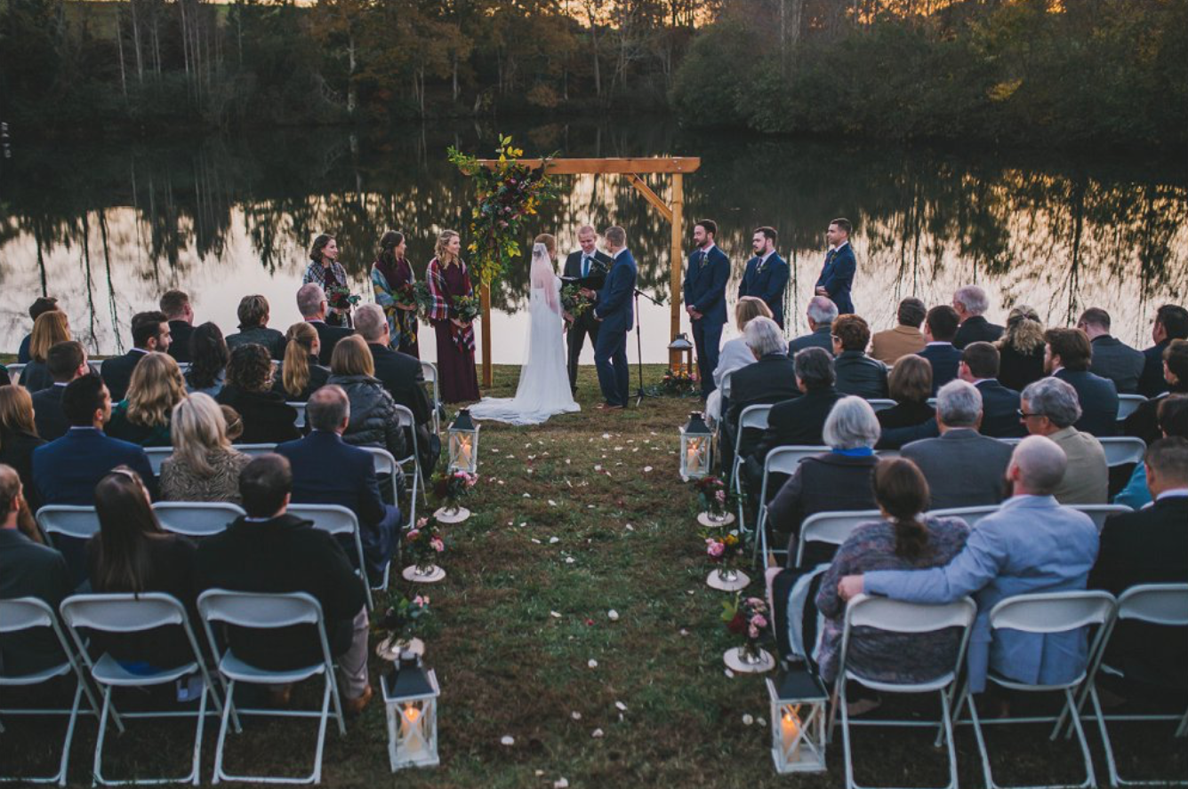 A wedding couple is getting married in front of a lake.