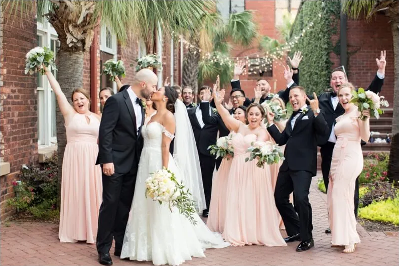A wedding couple is kissing each other and their guests are standing behind them and are cheering.