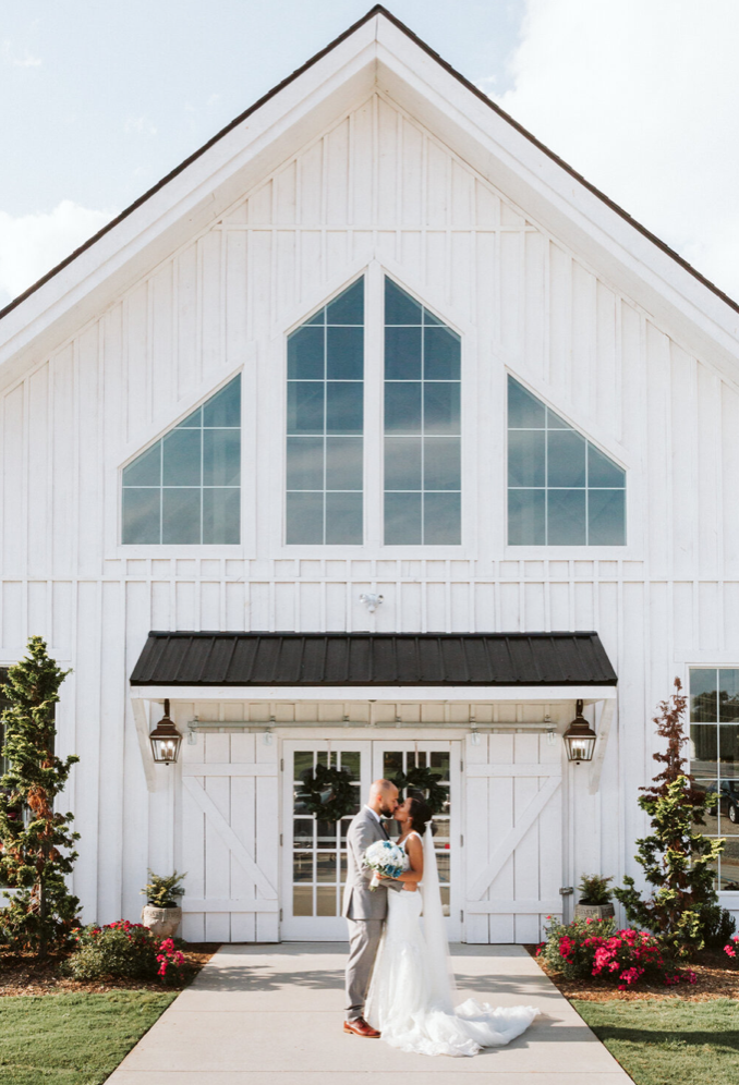 A wedding couple is kissing each other and standing in front of the Aurora Farm.