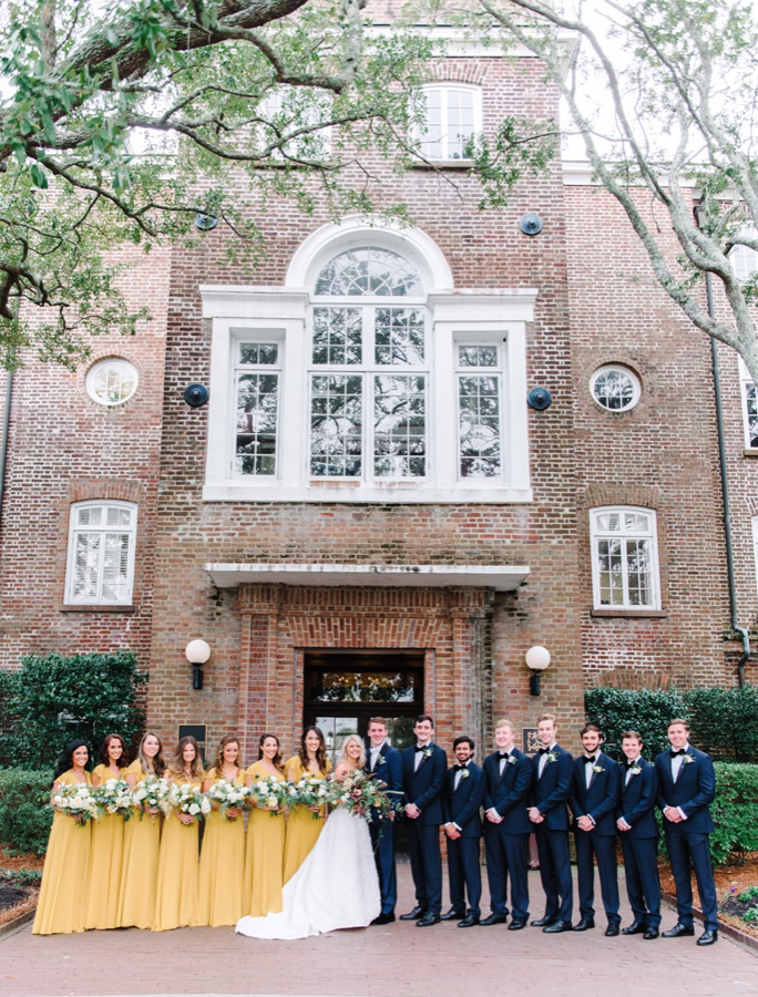 A wedding couple and their bridesmaids and groomsmen are standing in front of the Historic Rice Mill Building.