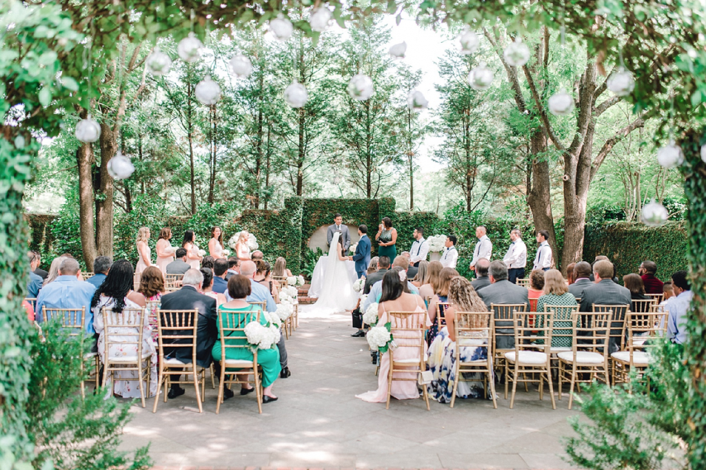 A wedding couple is standing at the altar and getting married, their guests are sitting in front of them.