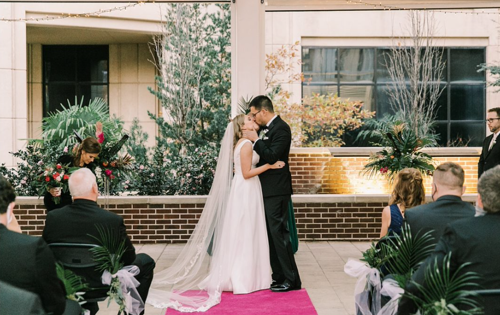 A wedding couple is kissing each other at the Columbia Museum of Art.