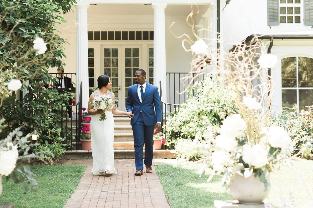 A wedding couple is holding hands and walking in front of the Belmont Hall venue in Delaware.