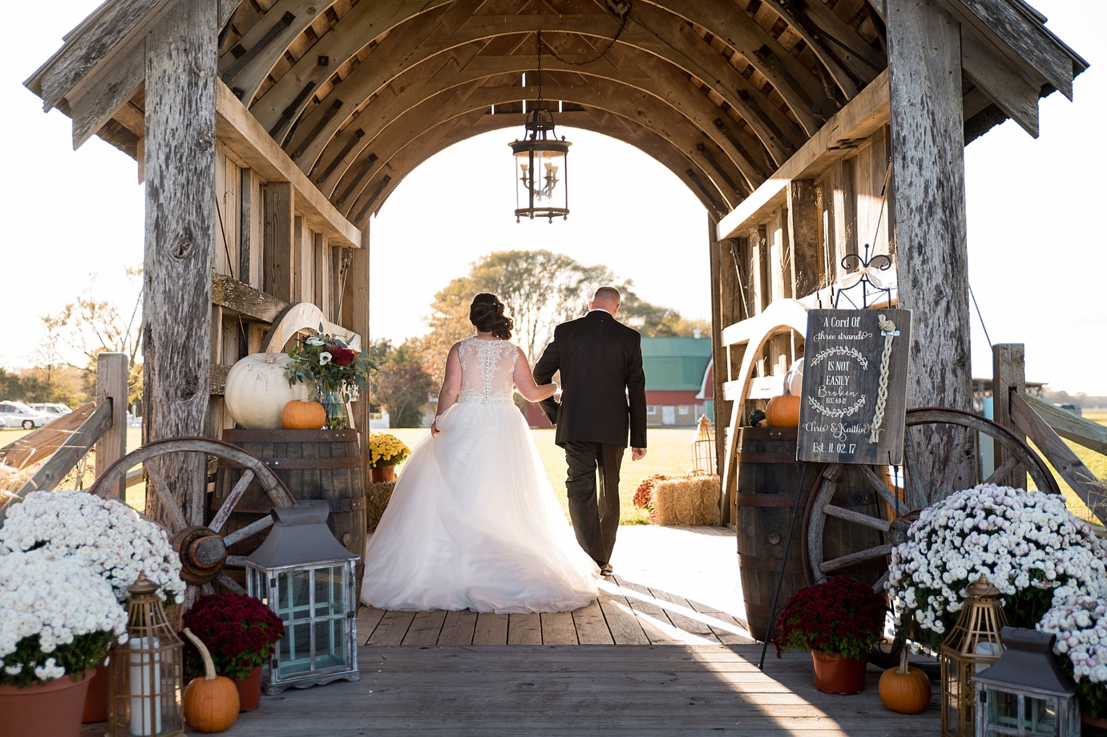 A wedding couple is holding hands and standing under a covered bridge.