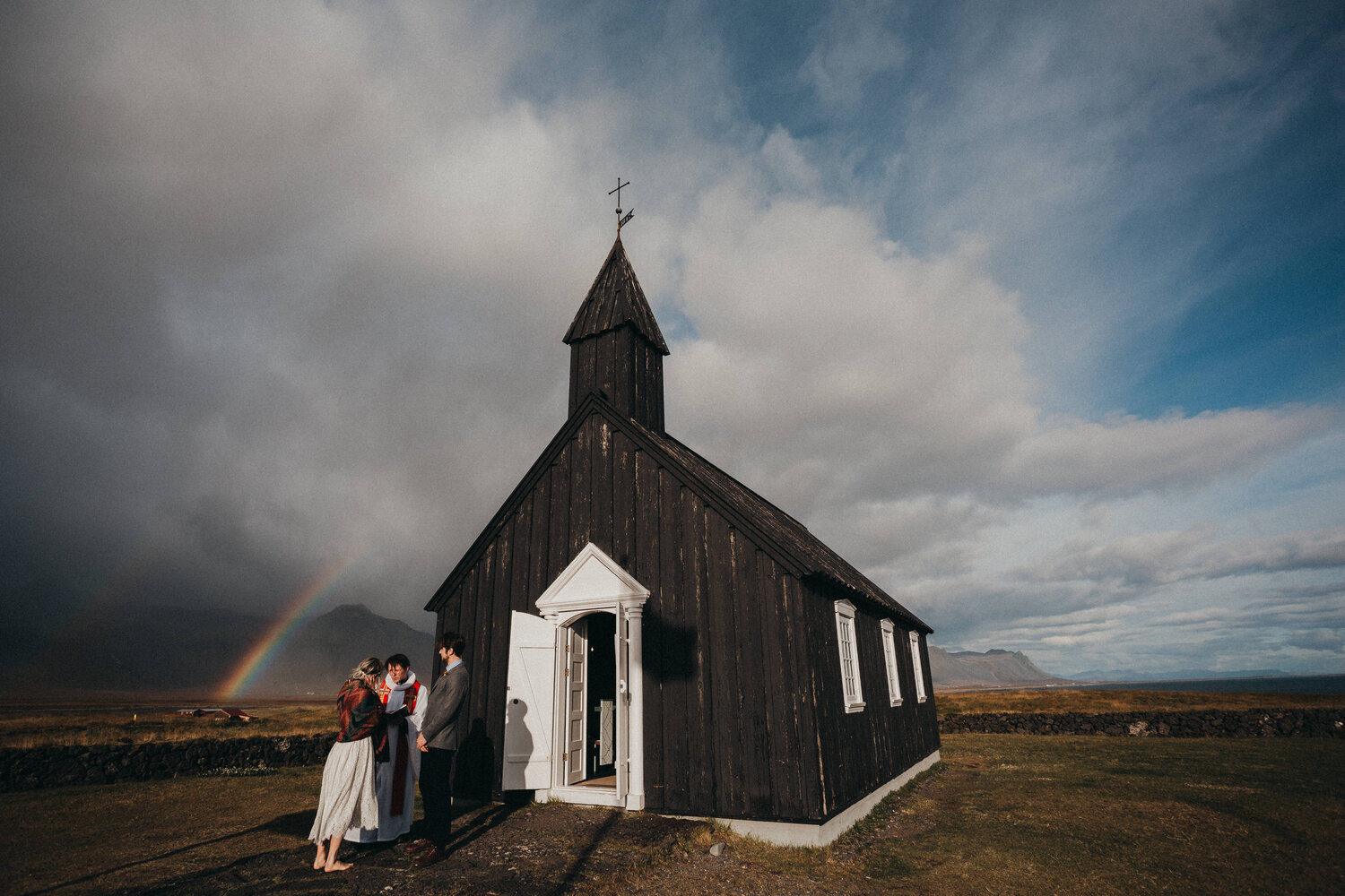 A wedding couple is getting married next to a church in Iceland.