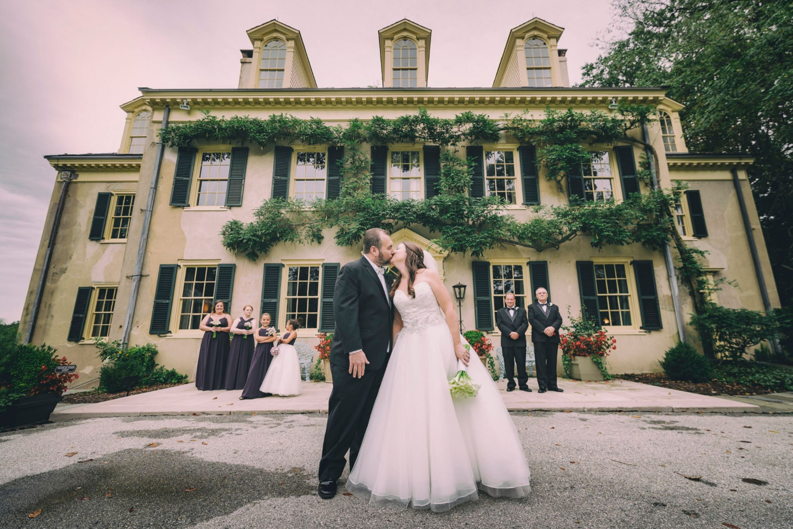 A wedding couple is kissing each other in front of a house.