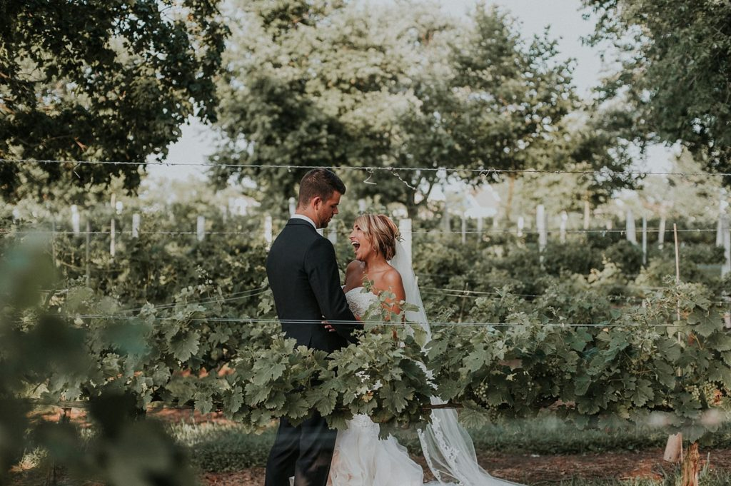 A wedding couple is holding each other at the Nassau Valley Vineyards in Delaware.